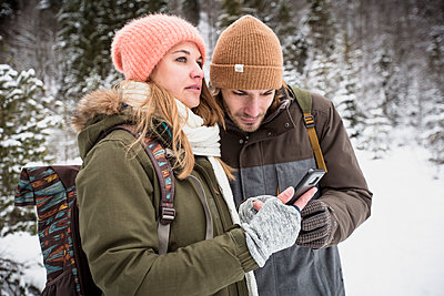 Couple on a trip in winter using cell phone - p300m1549810 by Sullivan