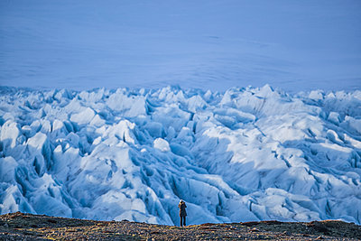 Person hiking and taking photos of a glacier along the South shore of Iceland; Iceland - p442m2077647 by Robert Postma