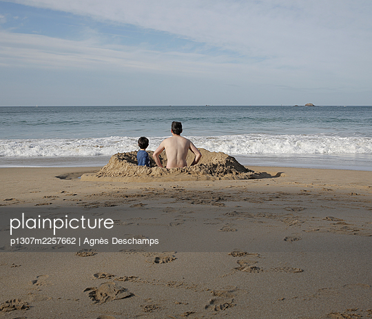 Father and Son Waiting for the High Tide in their Dam - p1307m2257662 by Agnès Deschamps