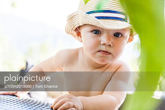 Portrait of curious baby boy wearing straw hat - p300m2013060 von Tom Chance