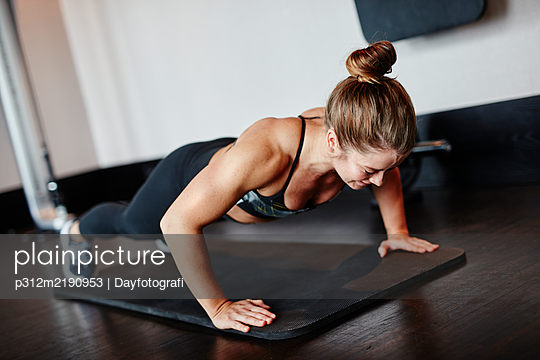 Woman doing push-ups in gym - p312m2190953 by Dayfotografi
