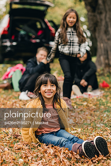Portrait of smiling girl sitting on autumn leaves during picnic - p426m2195271 by Maskot