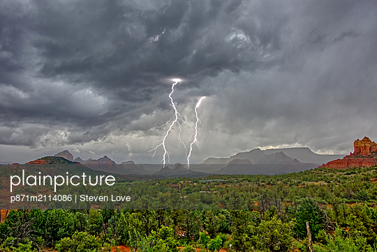 Lightning striking during a storm over Cibola Rock in Uptown, viewed from the Broken Arrow Trail, Sedona, Arizona, United States of America - p871m2114086 by Steven Love