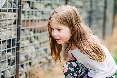 Young girl crouching down and looking for bugs in a rock wall - p1166m2201888 by Cavan Images