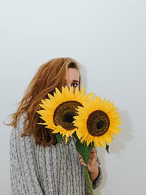 Girl hiding behind sunflower - p1507m2172043 by Emma Grann
