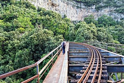 Greece, Pilion, Milies, back view of man walking on bridge along rails of Narrow Gauge Railway - p300m1581288 von Maria Maar