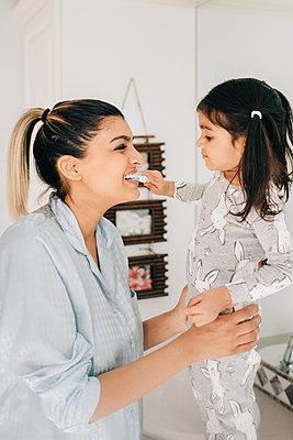 Girl brushing mother's teeth in bathroom - p924m2090638 by Sara Monika