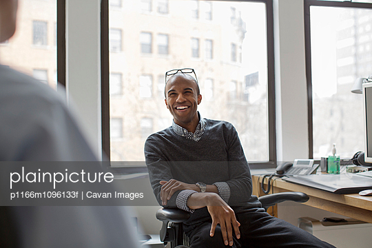 Happy businessman looking at coworker while sitting in office - p1166m1096133f by Cavan Images