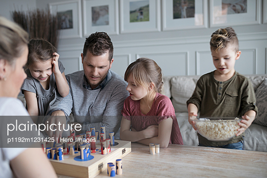 Young family playing game and eating popcorn in living room - p1192m1231425 by Hero Images