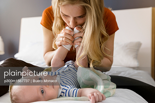 Mother kissing baby boy's feet - p300m1567737 by Buero Monaco