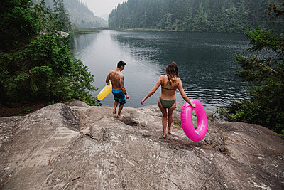Young couple with inflatable rings at remote lakeside, Squamish, British Columbia, Canada - p1023m2066796 by Jarusha Brown