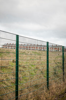 A row of Victorian Terraced houses in the distance behind a modern wire fence - p1302m1223564 by Richard Nixon