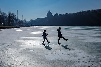 Two children playing on icy surface - p300m1588132 by Hans Mitterer