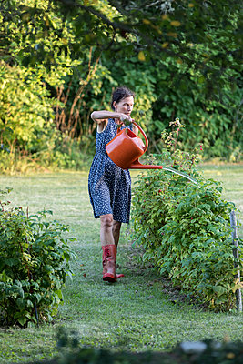 Woman watering plants in garden - p312m1533398 by Ulf Huett Nilsson