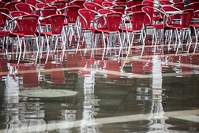 Cafe chairs in flooded St Mark's Square, Venice, Italy - p429m1504599 by WALTER ZERLA
