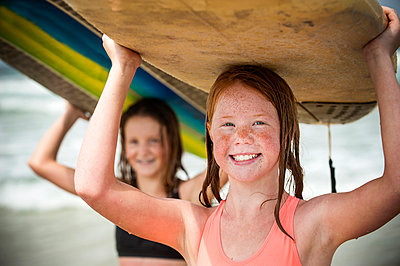 Portrait of smiling girls balancing surfboards on top of heads - p555m1231780 by Stephen Simpson Inc