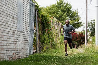 Black man running in urban grass - p555m1420901 by Roberto Westbrook