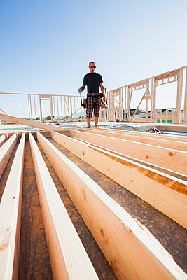 Caucasian man standing with frame on construction site - p555m1478658 by Mike Kemp