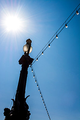 Light string hanging from a street lamp - p813m1057210 by B.Jaubert
