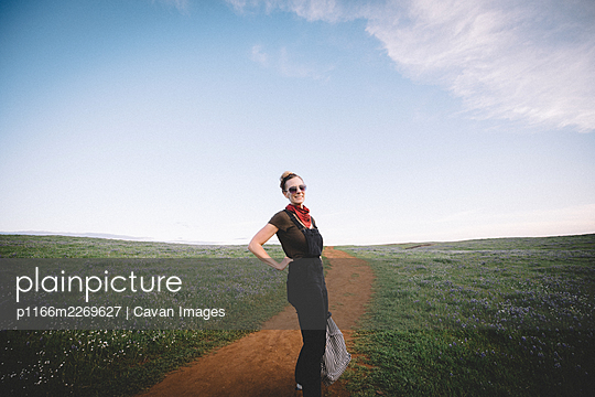 Woman Poses for a Photo on Grassy Mesa at Dusk - p1166m2269627 by Cavan Images