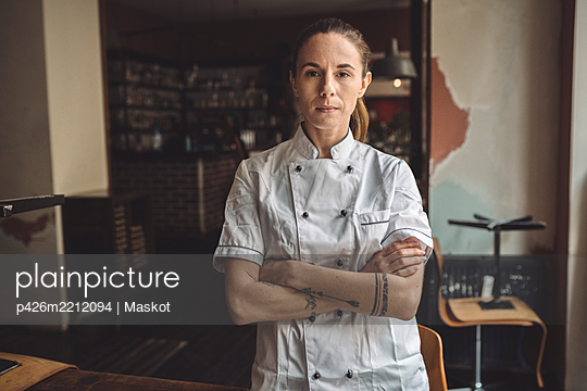 Portrait of chef with arms crossed standing in restaurant - p426m2212094 by Maskot