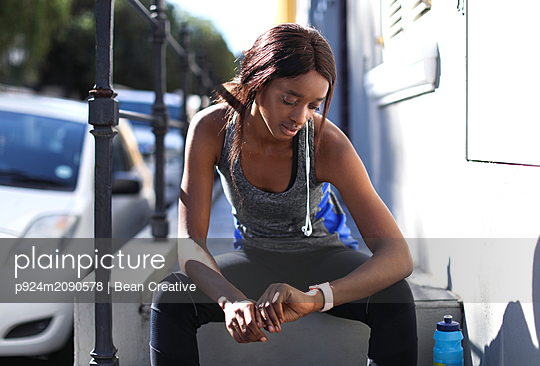 Young female runner sitting on city sidewalk looking at smartwatch - p924m2090578 by Bean Creative
