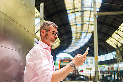 Side view of businessman using smart phone while standing by wall at railroad station platform - p1166m2060744 by Cavan Social