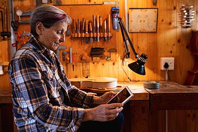 Female luthier using tablet in workshop - p1315m2131469 by Wavebreak