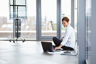 Businesswoman sitting on the floor in office using laptop - p300m2012980 by Rainer Berg