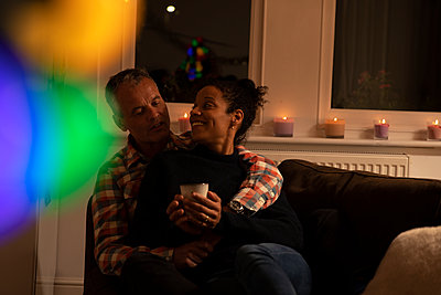 Smiling woman holding mug while relaxing with husband on sofa at home - p300m2243286 by Pete Muller