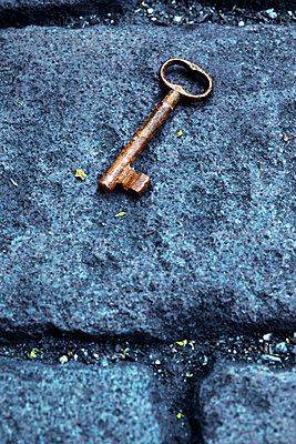 Old key lying on cobble stone pavement - p3300432 by Harald Braun