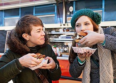 Two women eating hamburgers - p343m1168337 by Greta Rybus