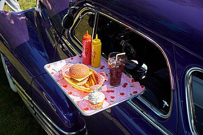 Typical American fast food on tray at vintage car, Chevrolet Fleetline - p300m2131752 von Bernados
