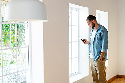 Young man at home checking his smartphone and standing in front of his windows in modern living room - p300m2180592 by Steve Brookland