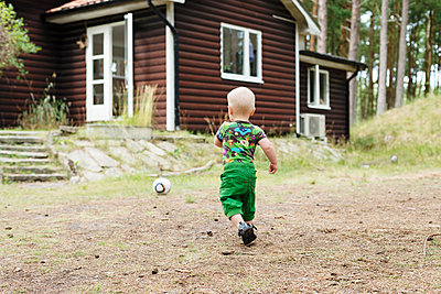 Boy playing in front of house in forest - p312m1164748 by Rebecca Wallin