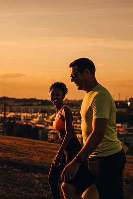 Smiling female and male athlete walking on land during sunset - p426m2270760 by Maskot
