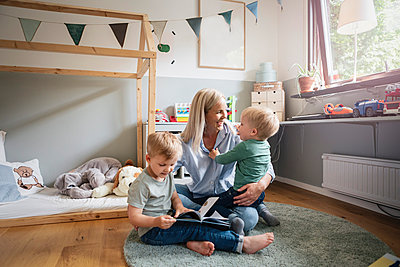 Cheerful mother playing with children in bedroom - p426m2270904 by Kentaroo Tryman