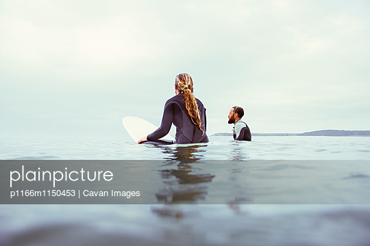 Male and female surfers relaxing in sea against cloudy sky - p1166m1150453 by Cavan Images