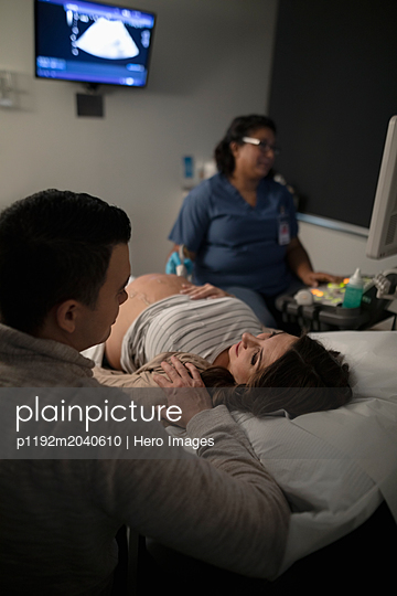Pregnant couple receiving ultrasound in clinic examination room - p1192m2040610 by Hero Images