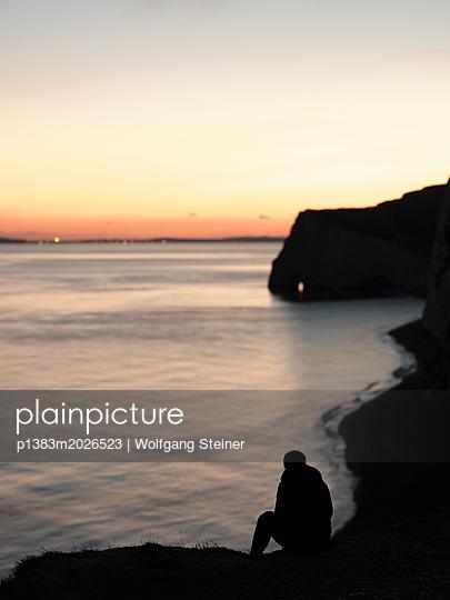 Frau sitzt an der Steilküste und beobachtet den Sonnenuntergang - p1383m2026523 von Wolfgang Steiner