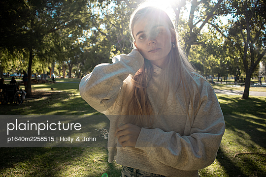 Teenage girl with blond hair in a park - p1640m2258515 by Holly & John