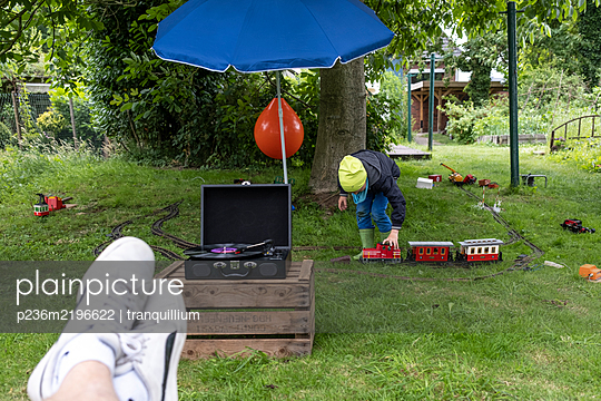 Child playing with toy train in the garden - p236m2196622 by tranquillium