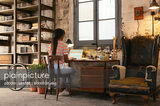 Back view of young woman sitting at desk in a loft working on laptop - p300m1581388 von Bonninstudio