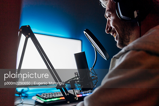 Smiling male gamer podcasting while playing game on computer at home - p300m2290650 by Eugenio Marongiu