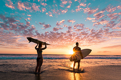 Rear view of couple with surfboards standing on shore during sunset - p1166m1210683 by Cavan Images