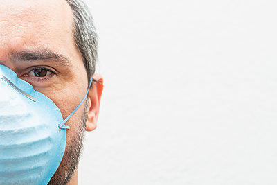 close up portrait of a tired man with a medical mask on a white - p1166m2179313 by Cavan Images