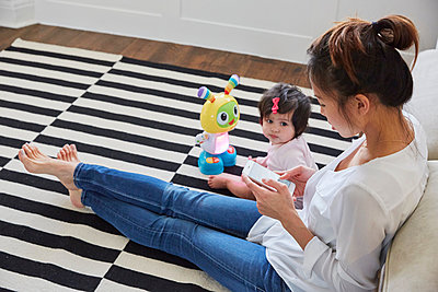 Woman with baby daughter sitting on floor using smartphone touchscreen - p429m1447824 by Emma Kim