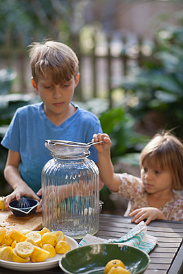Boy and two young sister preparing lemon juice for lemonade at garden table - p924m1446887 by Kinzie Riehm