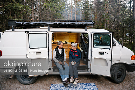 Senior couple relaxing, drinking coffee at camper van - p1192m2129188 by Hero Images