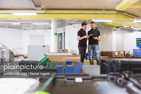 Two men with clipboard talking in factory - p300m1587593 von Daniel Ingold